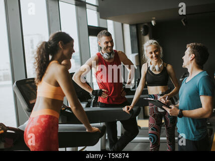 Group of young people in sportswear talking in a gym after a workout - Stock Photo