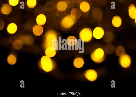 Abstract gold bokeh on black background. Defocused yellow lights, abstract texture. - Stock Photo