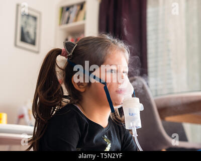 Cute caucasian girl at home taking inhalation from inhaler with oxygen mask - Stock Photo