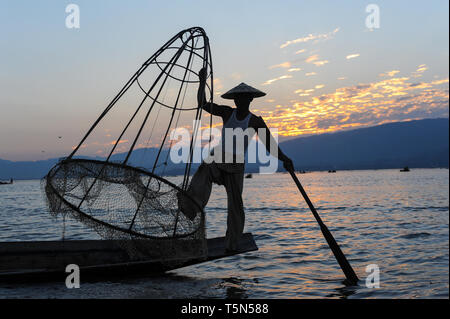 04.03.2014, Nyaungshwe, Shan State, Myanmar, Asia - A one-legged rower is seen fishing along the northern shore of the Inle Lake at dusk. - Stock Photo