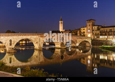 Ponte Pietra over Adige River and city at night in Verona. Italy - Stock Photo