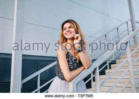 Portrait of beautiful model in grey shirt  leaning on handrail on stairs. She is smiling to side - Stock Photo