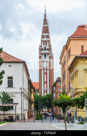 Szeged, Hungary, June 27: Citizens and visitors of the city are walking down the street. In the background is the Tower of the Cathedral of Szeged, Ju - Stock Photo