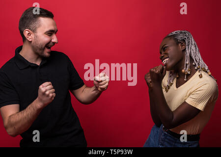 Portrait of man and woman in casual clothes screaming at each other standing face to face isolated over red background - Stock Photo
