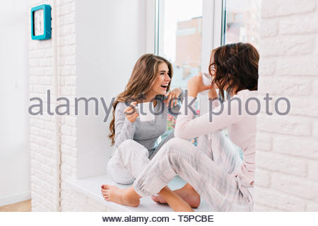 Two beautiful girls in pajamas drinking tea on window in light room. They smiling to each other - Stock Photo