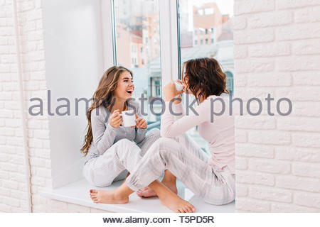 Two pretty girls in pajamas sitting on window in light room. They drinking tee and smiling to city outside - Stock Photo