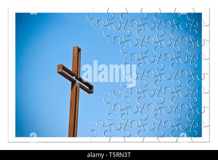 Rusty iron cross against a blue background - Rebuild our faith - Christian cross concept image in jigsaw puzzle shape. - Stock Photo