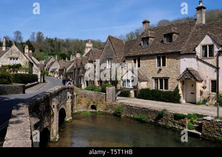 View of the river Bybrook and arched stone built bridge in Castle Coombe The Cotswolds Wiltshire England - Stock Photo