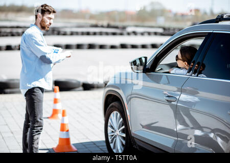 Male instructor teaching young woman driver to park a car on the training ground with traffic cones at the school - Stock Photo