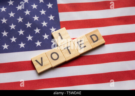 Maski, India 26, April 2019 : I voted wooden block letters,US elections on American flag. - Stock Photo