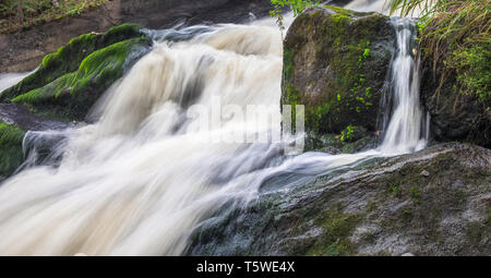 The rapid flow of the river, rocky coasts, rapids, bright green vegetation in Finland - Stock Photo