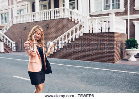 Fashionable woman with long hair walking in black dress on street on royal house background. She is speaking on phone, looking down - Stock Photo