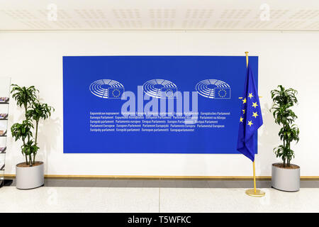 Front view of a large blue sign with the logo and the name of the European Parliament on the wall along with a european flag. - Stock Photo