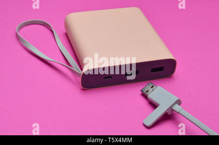 External battery for charging smartphones and gadgets with a usb cable close-up on a pink background. Power bank. Modern technologies. - Stock Photo
