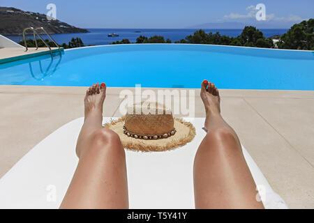 Female legs  sunbathing on patio chaise lounge  chair  near swimming pool . Stock image. - Stock Photo