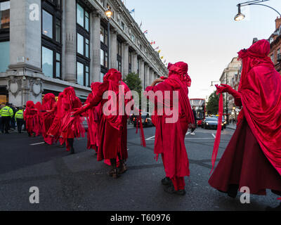 Extinction Rebellion environmental activist group, The Red Brigade seen protesting at Selfridges on Oxford Street on April 25, 2019 in London - Stock Photo