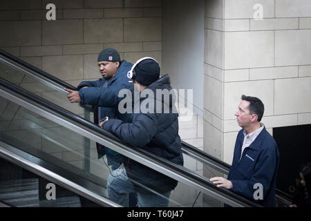 New York City, NY - March 07, 2017: Two unidentified man going up the escalator and talking in Penn Station, Manhattan, NY - Stock Photo