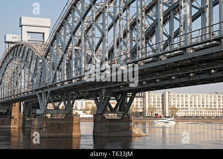 SAINT - PETERSBURG, RUSSIA – APRIL 26, 2019: Small white boat on The Neva River near The Finland Raiway Bridge in St Petersburg - Stock Photo