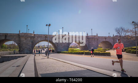 Madrid / Spain - 03 17 2019: People are walking next to the Toledo old bridge and doing sport at Madrid Rio green park along the Manzanares river - Stock Photo