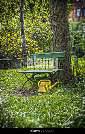 garden bench with yellow ewer - Stock Photo