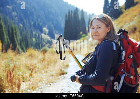 Portrait confident young female photographer backpacking on sunny trail - Stock Photo