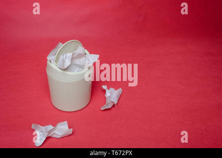 Light trash bin on a red background. Closeup of crumpled sheets of paper. The concept of environmental recycling of paper waste. - Stock Photo
