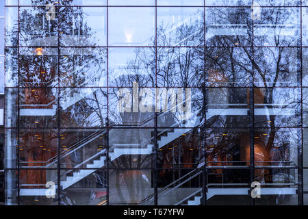 Modern architecture glass façade with indoors construction and stairs  reflecting trees in the park. Nature vs urban. Belgrade, Serbia. Abstract imag - Stock Photo