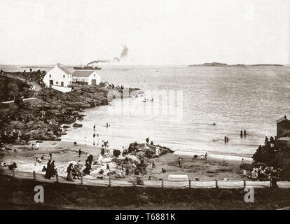 Late 19th Century view of the Bathing Place in Portrush, a small seaside resort town in County Antrim, Northern Ireland. Following the Wars of the Three Kingdoms in the mid-17th century, Portrush grew heavily from a small fishing town in the 19th century as a tourist destination, following the opening of the Ballymena, Ballymoney, Coleraine and Portrush Junction Railway in 1855. - Stock Photo