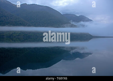 Dawn reflections on Lake McKerrow in the Hollyford Valley - Stock Photo