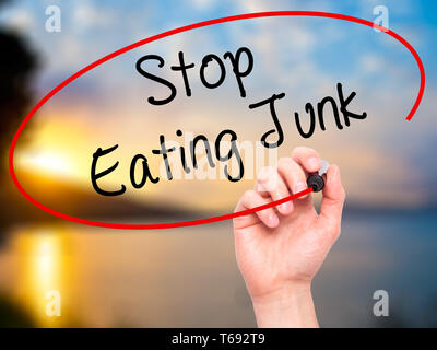 Man Hand writing Stop Eating Junk with black marker on visual screen. - Stock Photo
