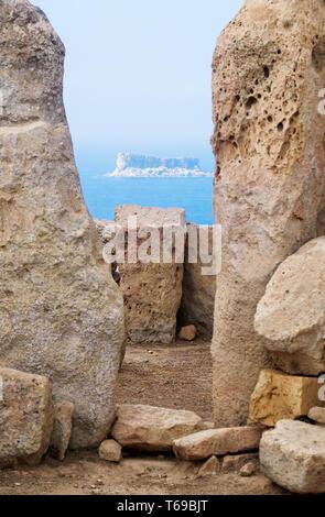 The view of Filfla through the foramen of two Orthostats of Hagar Qim, Malta - Stock Photo