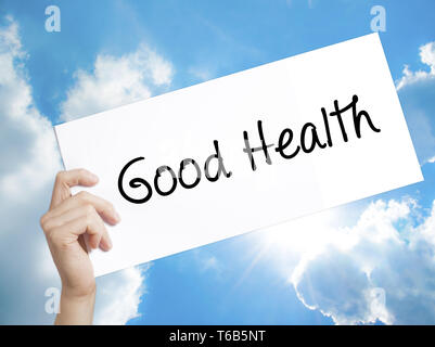 Good Health Sign on white paper. Man Hand Holding Paper with text. Isolated on sky background - Stock Photo