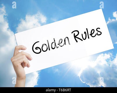 Golden Rules Sign on white paper. Man Hand Holding Paper with text. Isolated on sky background - Stock Photo