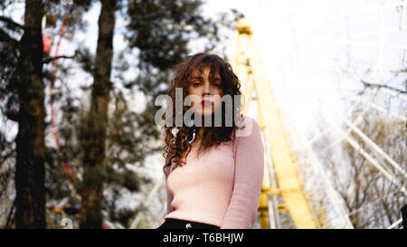 Women with long curly hair in the background of the Ferris wheel in sunny day - Stock Photo