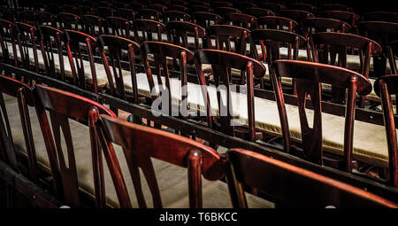 Wooden chairs in a row in a church - Stock Photo
