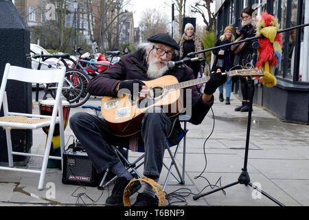 A senior busker playing guitar, Portobello Road market, London - Stock Photo