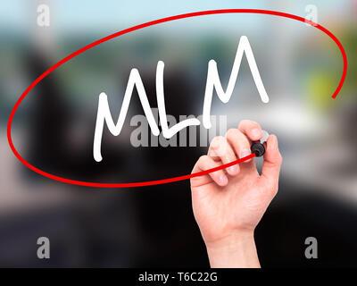 Man Hand writing  MLM (Multi-Level Marketing) with black marker on visual screen - Stock Photo