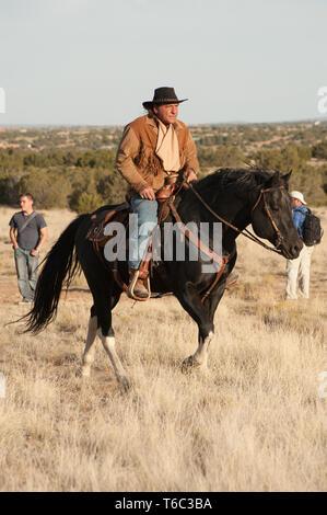 Cowboy rides a black horse. - Stock Photo