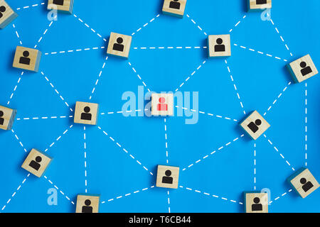 Leadership and network teamwork concepts Red businessman icon on the wooden block in the middle between the black business icon on the wooden blocks.  - Stock Photo