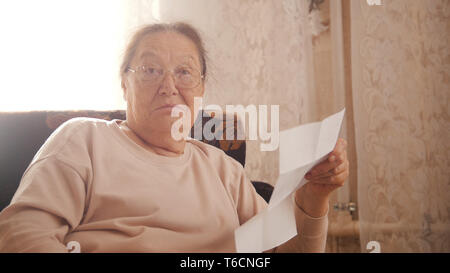 An old amazed woman in glasses sitting in the armchair, holding an utility bills and looking in the camera - Stock Photo