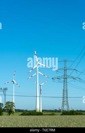 Overhead lines and wind engines on a sunny day seen in Germany - Stock Photo