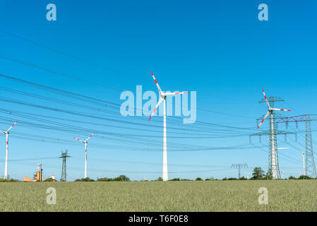 Wind engines and power supply lines on a sunny day seen in Germany - Stock Photo