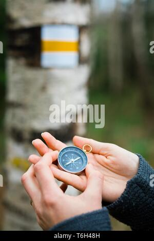 Woman's hands using compass by tourist sign - looking for the right direction - Stock Photo