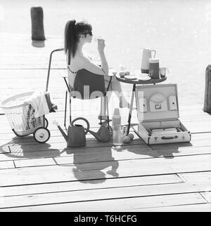 1960s lifestyle. A young woman sitting in the sun wearing a bikini. In the picture there are many of the timely objects made of plastic that were popular at the time. Especially when being on a summer vacation or camping. A set of cups and saucers on the table. A practical case to transport them in. Sweden 1960s Photo Kristoffersson ref DB85-2 - Stock Photo