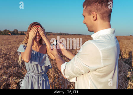 Happy young couple love, summer wheat field. The girl closed her eyes. A man makes a wedding proposal marriage. Emotions happiness surprise, love - Stock Photo