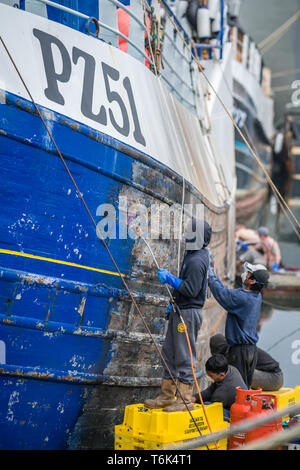 Men repairing and painting large boat - Stock Photo