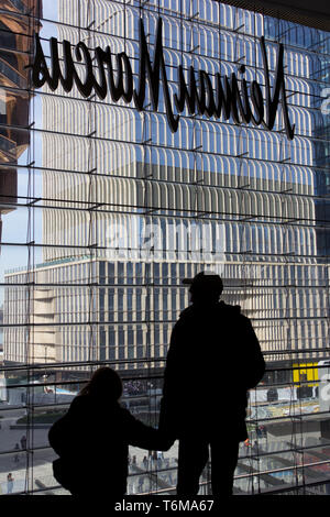 In a silhouetted back view, a man wearing a baseball cap holds the hand of a young girl as they look through a window of the Hudson Yards mall out onto the temporarily named Vessel steel sculpture partially visible on the left, with a high-rise building still under construction to the right, and people in the courtyard below. Above their heads is the reverse side of a Neiman Marcus department store sign. The Hudson Yards complex, which debuted 15 March 2019, to controversy about whether it was too elitist, encompasses retail, residential, restaurants, cultural institutions, and public space. - Stock Photo