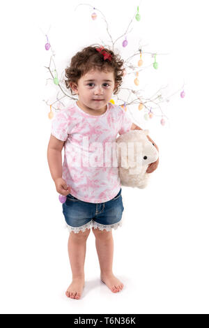Toddler with Easter eggs hugs Easter lamb plush toy, isolated on white. - Stock Photo