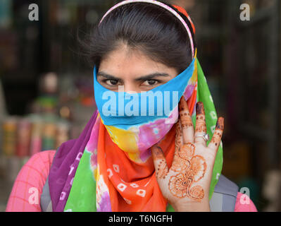 Young Indian Rajasthani woman covers her face with a colourful secular dust veil and shows the intricate henna tattoos on her left palm. - Stock Photo