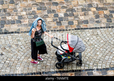Lviv, Ukraine - July 31, 2018: Aerial view in historic Ukrainian city in old town market square with people woman under jacket cover from rain pushing - Stock Photo
